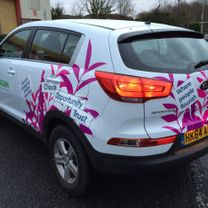 A large corporation decorated Kia vehicle decorated in a pink, leafy company design complete with corporate logo
