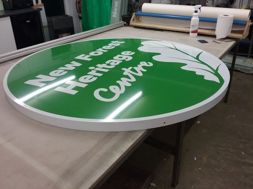 Besoke made circular tray with green vinyl applied to make up company name and decorative leaf design