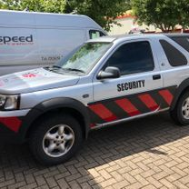 A security guard Landrover with bespoke chevron decals along the lower sinde panels and front bumper, with company logo decals