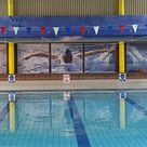 An indoor leisure centre swimming pool area with printed pull down blinds