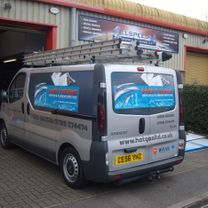 A plumbers vehicle with printed vinyl graphics in the panels and company details along the sides and back