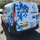 A pharmacy vinyl wrap vehicle with company logo and contact details