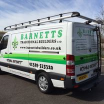 A tradesmans van decorated in company logo, contact details and striping along the sides and rear