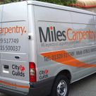 An individual tradesman decorated vehicle in vinyl graphics with striping down the side