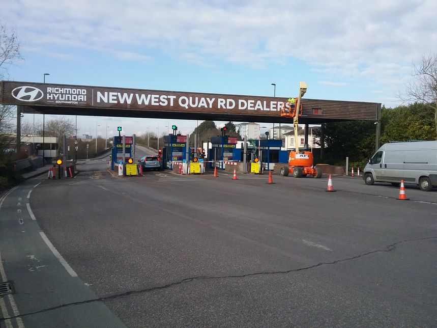 A large format sign being installed by our fully trained sign fitter using a cherry picker, over a toll bridge